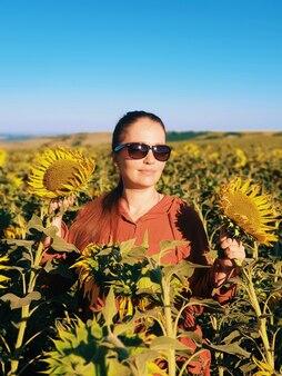 Portrait d'une femme à lunettes de soleil dans un champ de tournesols