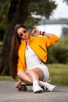 Portrait femme avec lunettes de soleil et tenue sportive avec une veste orange sur une planche à roulettes au parc