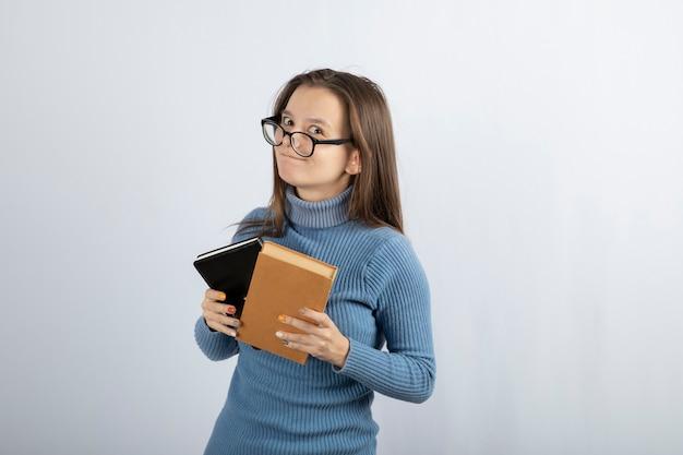 Portrait d'une femme à lunettes tenant deux livres sur fond blanc-gris.