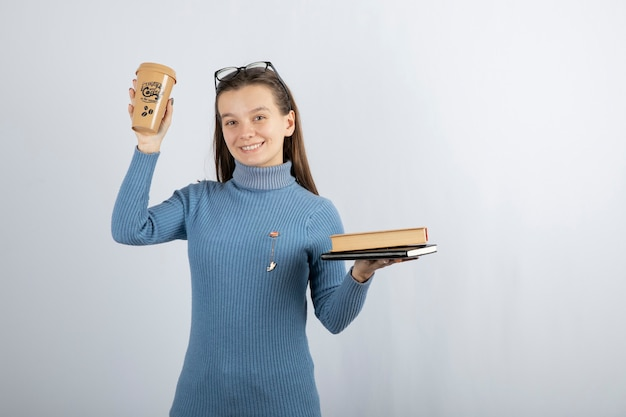 Portrait d'une femme à lunettes tenant deux livres et une tasse de café.