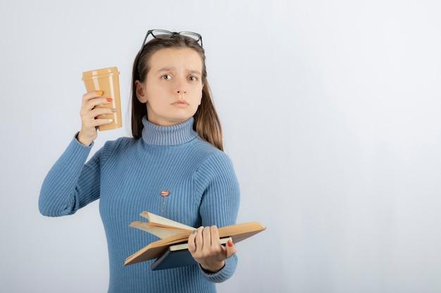 Portrait d'une femme à lunettes tenant un livre et une tasse de café.