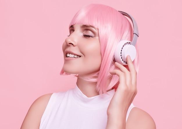 Portrait de femme magnifique aux cheveux roses aime la musique dans les écouteurs