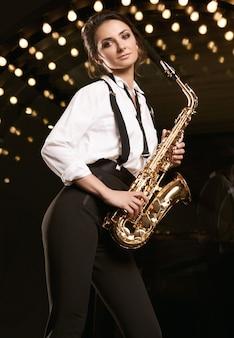 Portrait de femme magnifique modèle brune en costume formel à la mode avec saxophone