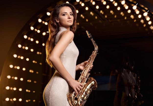 Portrait de femme magnifique modèle brune en robe élégante avec saxophone jouant sur les projecteurs de la scène du restaurant.
