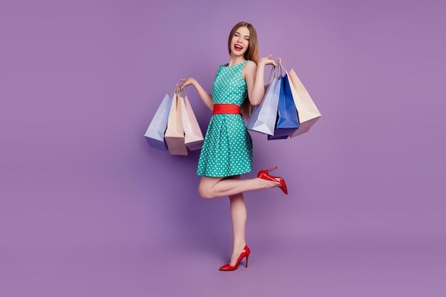 Portrait d'une femme magnifique tenant de nombreux colis portant une robe courte à talons hauts sur fond violet