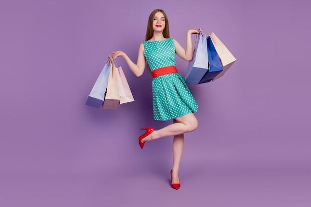 Portrait de femme magnifique tenir de nombreux sacs de magasin posant porter une mini robe à talons hauts sur fond violet