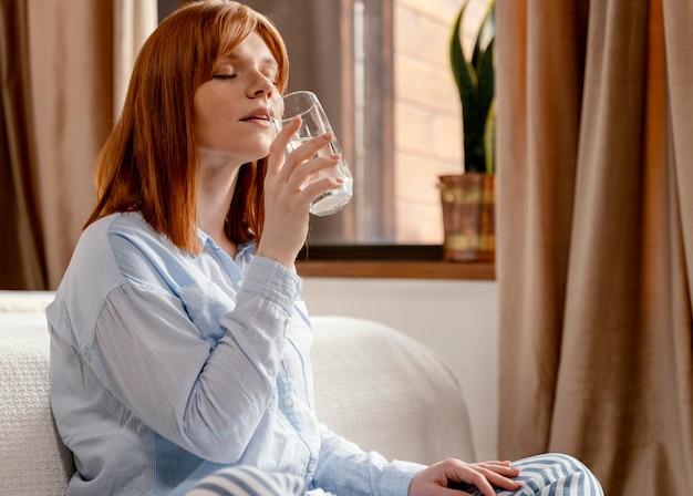 Portrait femme à la maison, boire un verre d'eau