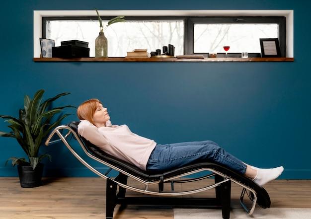 Portrait femme à la maison de détente sur une chaise
