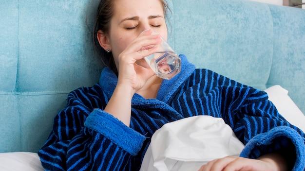 Portrait d'une femme malade allongée dans son lit et buvant de l'eau.