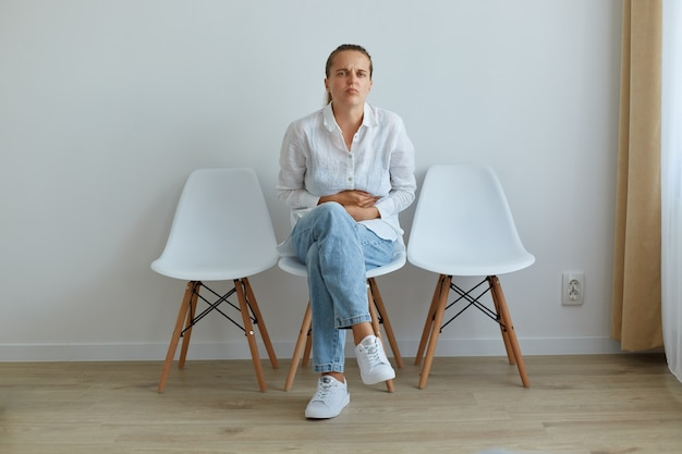 Portrait d'une femme malade aux cheveux noirs et queue de cheval, vêtue d'une chemise blanche et d'un jean, assise sur une chaise en file d'attente pour le médecin de la clinique, souffrant de terribles maux d'estomac.