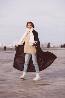 Portrait de femme en manteau noir d'hiver et écharpe blanche sur la place de la ville.