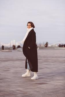 Portrait De Femme En Manteau Noir D'hiver Et écharpe Blanche Sur La Place De La Ville. Photo gratuit
