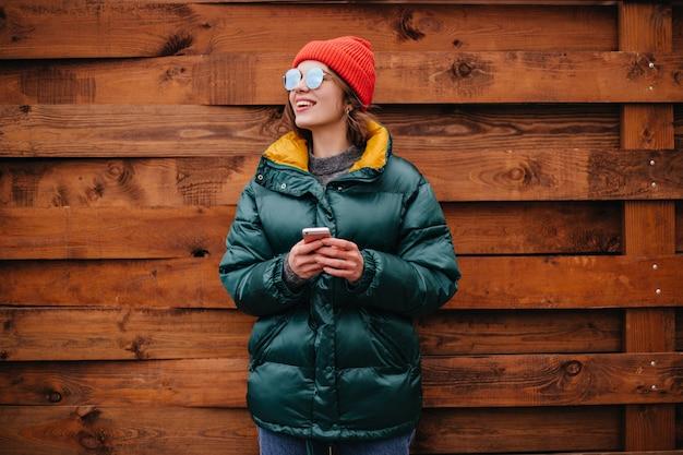 Portrait de femme en manteau vert émeraude sur mur en bois