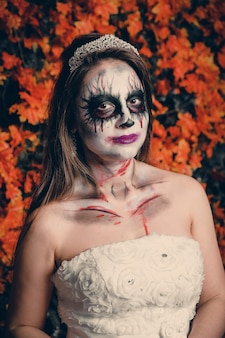 Portrait d'une femme avec maquillage fantôme et robe de mariée.