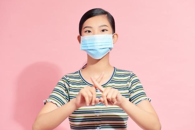 Un portrait de femme avec un masque médical facial montrant un geste d'arrêt. concept de personnes, de soins de santé et de médecine