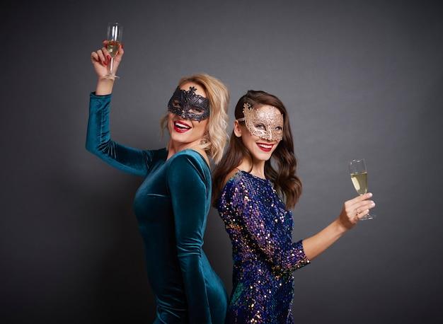 Portrait de femme avec des masques et du champagne à la fête