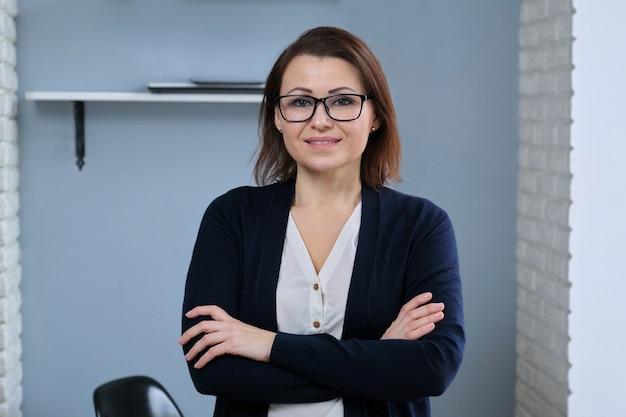Portrait de femme mature confiante positive avec les bras croisés, femme médecin, psychiatre, psychologue, thérapeute travaillant au bureau, souriant regardant la caméra