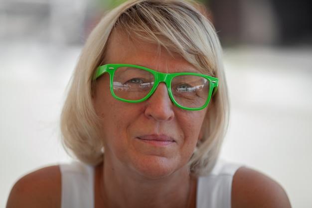 Un portrait de femme mature avec des lunettes vertes