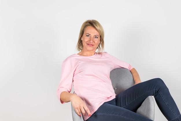 Portrait de femme mature reposante sur une chaise grise sur fond blanc