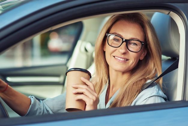 Portrait d'une femme mature souriante portant des lunettes assis derrière le volant de son moderne