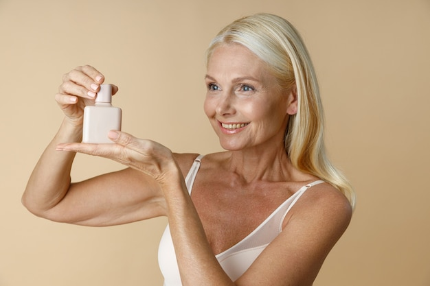 Portrait d'une femme mature souriante en sous-vêtements regardant loin la publicité et tenant un pot blanc de