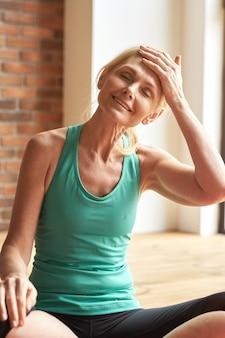 Portrait d'une femme mature sportive heureuse souriante les yeux fermés et s'essuyant le front assis