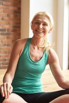 Portrait d'une femme mature sportive joyeuse souriante à la caméra assise sur le sol après une intensification