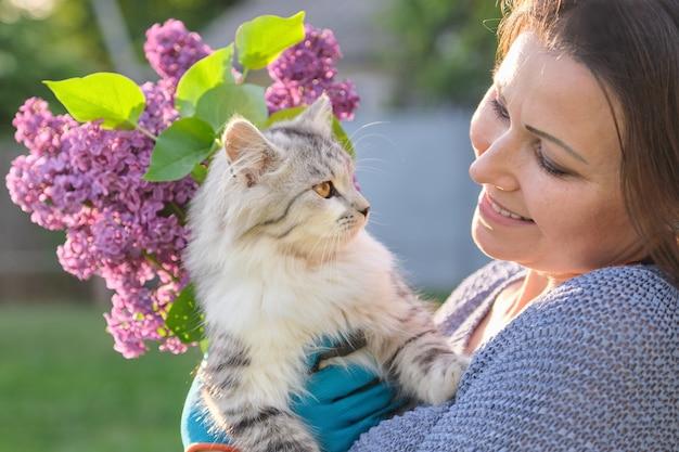 Portrait de femme mature tenant animal chat pelucheux gris dans ses bras, femme à l'extérieur dans le jardin