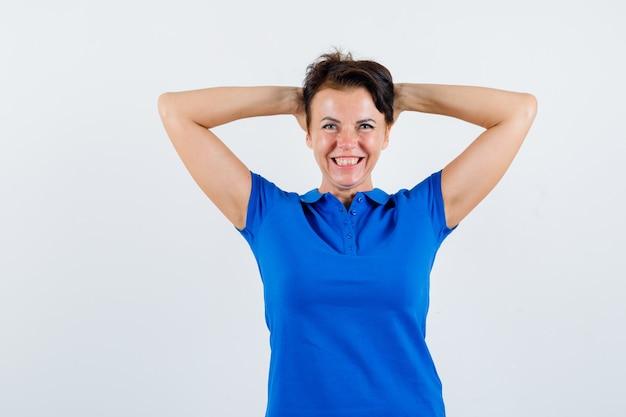 Portrait de femme mature tenant les mains derrière la tête en t-shirt bleu et à la vue de face heureux