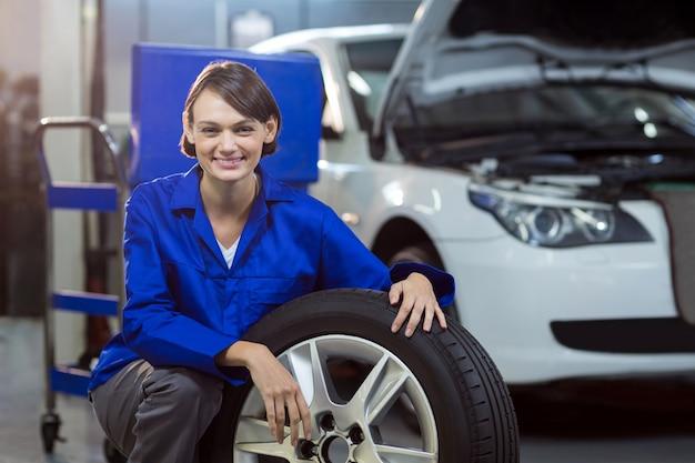 Portrait de femme mécanicien avec un pneu