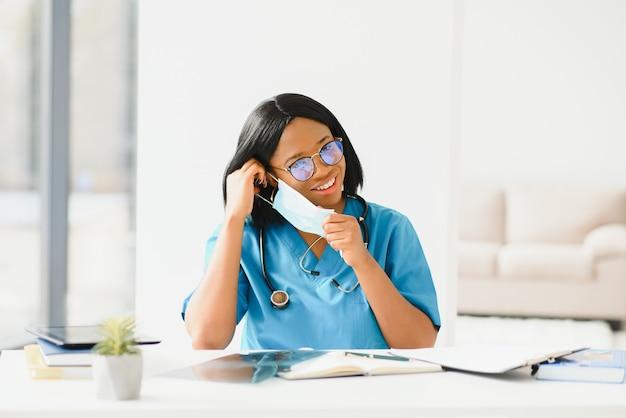 Portrait de femme médecin afro-américaine belle en masque médical regardant la caméra. gros plan femme médecin en protection respiratoire.