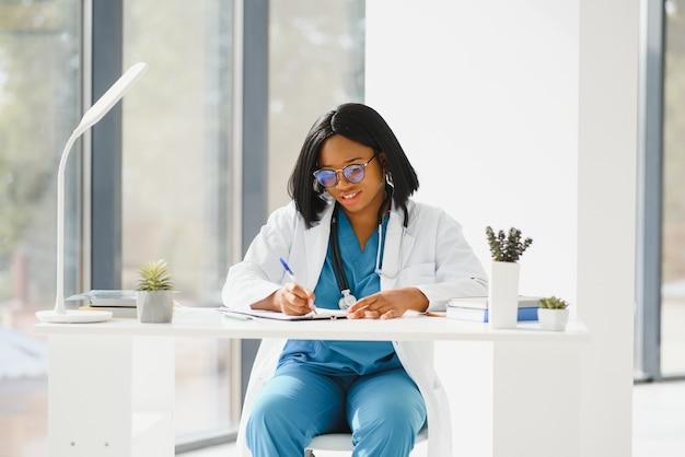 Portrait de femme médecin afro-américaine souriant à l'hôpital