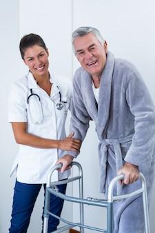 Portrait de femme médecin aidant un homme senior à marcher avec une marchette