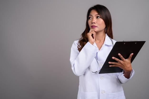 Portrait de femme médecin asiatique tenant le presse-papiers