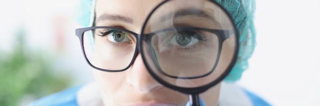 Portrait de femme médecin dans des verres regarde à travers une loupe grossissante