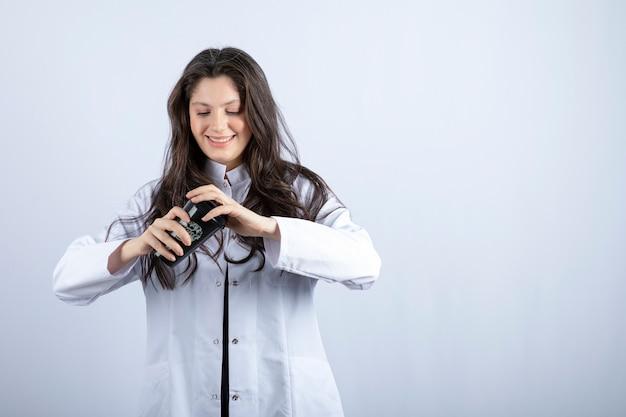 Portrait de femme médecin fermant le couvercle de la tasse de café sur le mur blanc.