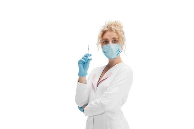 Portrait de femme médecin, infirmière ou cosmétologue en uniforme blanc et gants bleus sur fond blanc.