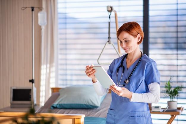 Un portrait d'une femme médecin ou d'une infirmière debout dans une chambre d'hôpital, à l'aide d'une tablette.