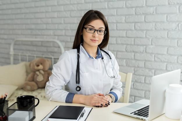 Portrait d'une femme médecin joyeuse et heureuse assise sur son lieu de travail