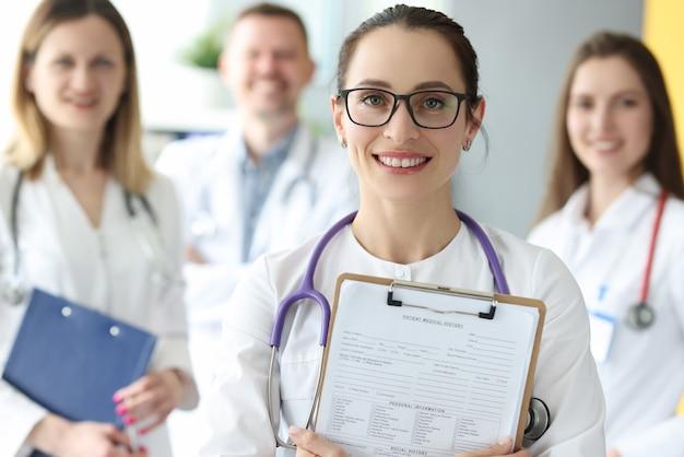 Portrait de femme médecin à lunettes avec antécédents médicaux du patient en mains avec des collègues