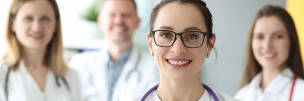 Portrait de femme médecin à lunettes avec antécédents médicaux du patient en mains sur fond de collègues