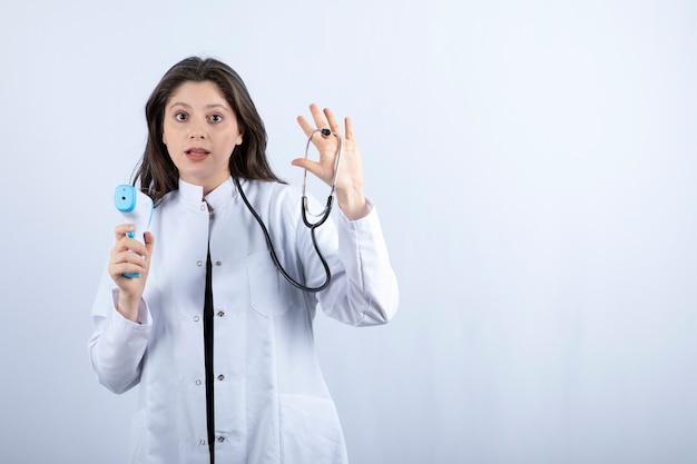 Portrait de femme médecin montrant un thermomètre et un stéthoscope sur fond gris.