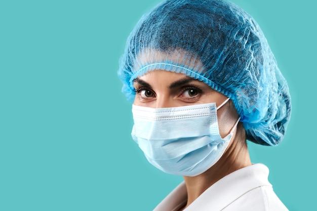 Portrait d'une femme médecin portant un masque médical de protection isolé sur fond bleu
