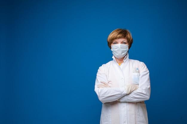 Portrait de femme médecin professionnel en uniforme blanc et masque de protection posant isolé