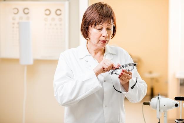 Portrait d'une femme médecin senior en uniforme debout dans le cabinet ophtalmologique