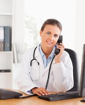 Portrait d'une femme médecin sérieuse au téléphone