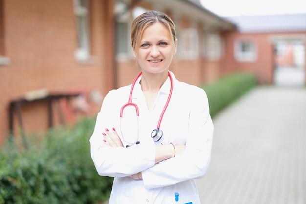 Portrait d'une femme médecin souriante avec les bras croisés dans la rue