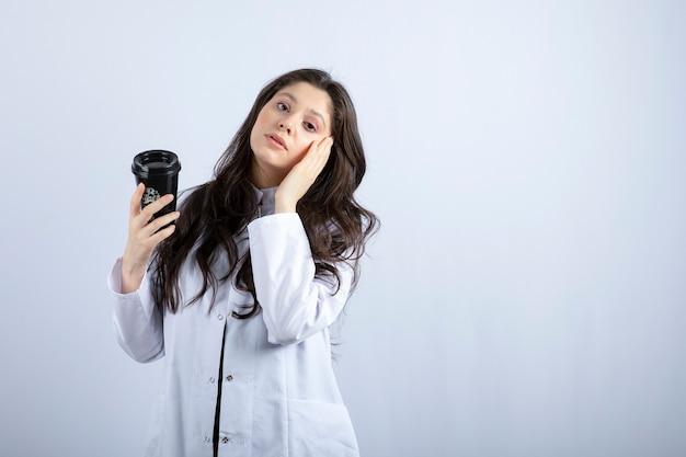 Portrait de femme médecin avec tasse de café debout sur fond gris.