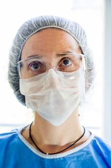 Portrait de femme médecin, visage de jeune fille médecins avec masque et uniforme de verre de sécurité. uniforme pour la chirurgie et les virus. fermer.