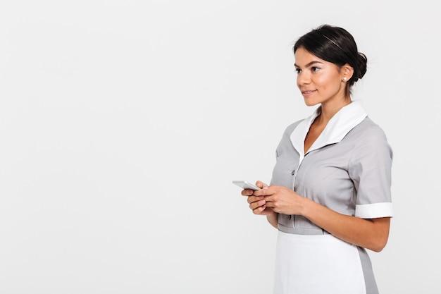 Portrait de femme de ménage brune en uniforme tenant un téléphone mobile et regardant de côté